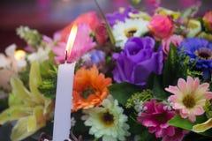Świeczka z pięknym bukietem różni kwiaty, plamy backgr Zdjęcia Royalty Free