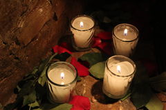 Świeczki między różanymi płatkami Fotografia Royalty Free