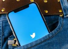 Świergot podaniowa ikona na Jabłczanego iPhone X smartphone parawanowym zakończeniu w cajgach wkładać do kieszeni Świergotu app i zdjęcia stock