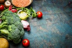 Świezi brokuły, różnorodni warzywa, czerwona soczewica i składniki dla gotować na nieociosanym drewnianym tle, granica Fotografia Stock