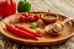 Świezi czereśniowi pomidory, czosnków cloves, basilów liście, mieszanka suche pikantność na drewnianej tacy zdjęcia royalty free