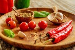 Świezi czereśniowi pomidory, czosnków cloves, chili pieprze, basilów liście, mieszanka suche pikantność w drewnianym garnku z łyż fotografia stock
