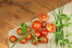 Świezi czereśniowi pomidory na nieociosanym drewnianym tle świezi kuchennego stołu warzywa Zdjęcie Stock