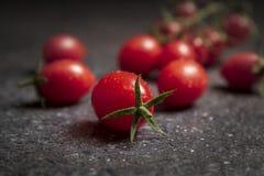 Świezi czerwoni czereśniowi pomidory na zmroku drylują tło obraz royalty free