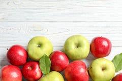 Świezi czerwoni i zieleni jabłka na białym drewnianym tle Obraz Stock