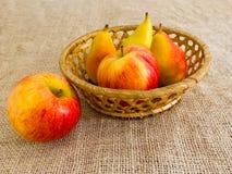 Świezi czerwoni jabłka i bonkrety w słomianym koszu Obrazy Royalty Free