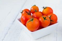 Świezi czerwoni pomidory w białym pucharze na białym drewnianym stole Zdjęcie Stock