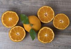 Świezi dojrzali tangerines z liśćmi na drewnianym tle obrazy royalty free