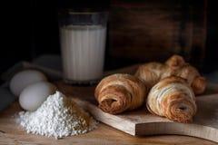 Świezi gotujący croissants na tnącej desce z mąką, mleko, jajka świeży ciasto, piekarnia Zdjęcie Stock