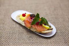 Świezi Hiszpańscy tapas na chlebowym baguette dymili Norweskiego łososia z masłem, ziele i cebulami czarnej oliwki, Znakomity tło zdjęcia royalty free