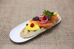 Świezi Hiszpańscy tapas na chlebowym baguette dymili Norweskiego łososia z masłem, ziele i cebulami czarnej oliwki, Znakomity tło obraz stock