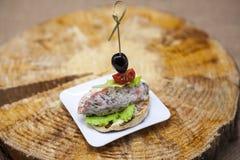 Świezi Hiszpańscy tapas na chlebowym baguette dymili Norweskiego łososia z masłem, ziele i cebulami czarnej oliwki, Znakomity tło obrazy royalty free