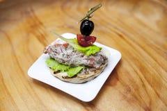 Świezi Hiszpańscy tapas na chlebowym baguette dymili Norweskiego łososia z masłem, ziele i cebulami czarnej oliwki, Znakomity tło zdjęcie royalty free