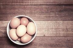 Świezi jajka, Świezi jajka w filiżance na drewnianym tle Fotografia Royalty Free