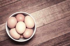 Świezi jajka w filiżance na drewnianym tle Obrazy Royalty Free