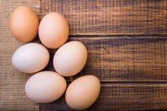 Świezi jajka zbliżają banatki na drewnianym tle Odgórny widok wieśniak kosmos kopii Obraz Stock