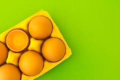 Świezi kurczaków jajka w pudełku na zielonym tle obraz royalty free
