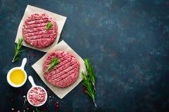 Świezi minced wołowina mięśni hamburgery z pikantność na ciemnym tle Surowy zmielony wołowiny mięso zdjęcie royalty free