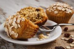 Świezi muffins z oatmeal piec z wholemeal mąką na bielu talerzu, wyśmienicie zdrowy deser Zdjęcia Royalty Free
