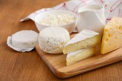 świezi nabiałów produkty Mleka, sera, brie, camembert i chałupy ser na drewnianym tle, Obraz Royalty Free