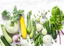 Świezi ogrodowi sezonowi warzywa - kalarepy, zucchini, kabaczek, ogórki, chard, zieleni grochy, cebule, czosnek na lekkim tle, fotografia stock