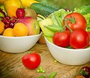 Świezi organicznie owoc i warzywo w pucharach Fotografia Royalty Free