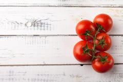 Świezi organicznie pomidory na białym drewnianym stole, odgórny widok kosmos kopii Zdjęcia Royalty Free