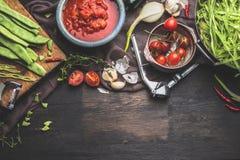 Świezi organicznie sezonowi warzywa na ciemnym nieociosanym drewnianym tle Pomidory, zieleni francuskie fasole i kulinarni składn obraz royalty free