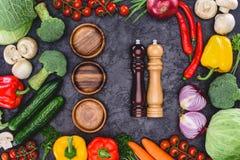Świezi organicznie warzywa, drewniani talerze i zbiorniki dla pikantność na czerni, Fotografia Stock