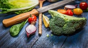 Świezi organicznie warzywa z kuchennym nożem na błękitnym drewnianym tle Zdjęcie Stock