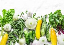 Świezi organicznie warzywa - zucchini, kabaczek, ogórki, brokuły, cebule, czosnek, chard, zieleni grochy na lekkim tle, wierzchoł Fotografia Royalty Free