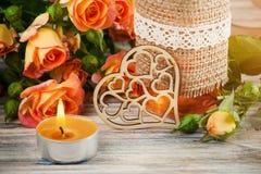 Świezi pomarańczowi róża kwiaty, serce, wystrój butelka i zaświecająca świeczka, Zdjęcia Stock