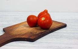 Świezi pomidory na rocznik drewnianej tnącej desce i drewna tle Obrazy Royalty Free