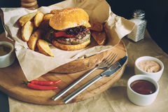 Świezi smakowici hamburgery z francuskimi dłoniakami i kumberlandem na drewnianym stołowym wierzchołku zdjęcia stock