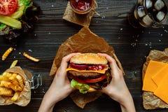 Świezi smakowici hamburgery z francuskimi dłoniakami, kumberlandem i napojem na drewnianym stołowym odgórnym widoku, Obraz Royalty Free