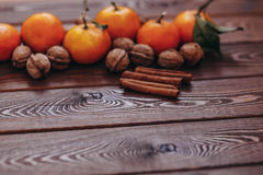 Świezi soczyści dojrzali tangerines z liścia cynamonem na drewnianym backgroun i orzechami włoskimi Zdjęcia Royalty Free