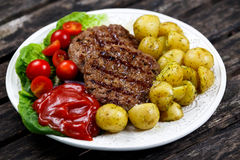 Świezi soczyści grillów hamburgery, słuzyć z ketchupem, młodymi grulami, pomidorami i warzywami, głębii pola płycizny stół drewni Fotografia Stock