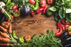 Świezi surowego warzywa składniki dla zdrowy kulinarnego lub sałatka robi nad nieociosanym drewnianym tłem, odgórny widok, kopii  Fotografia Stock
