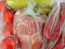 Świezi surowi foods w plastikowych workach właśnie kupowali ciężarem: kawałek wieprzowiny mięso, dwa zucchini, few czerwoni pomid obrazy royalty free