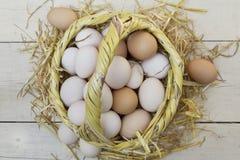 Świezi surowi jajka w słomianym koszu zdjęcie stock