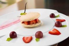 Świezi truskawkowi i kremowi macaroons słuzyć z winogrona i truskawki segmentami Obraz Royalty Free