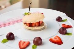 Świezi truskawkowi i kremowi macaroons słuzyć z winogrona i truskawki segmentami Zdjęcie Royalty Free