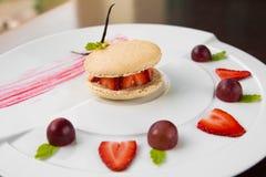 Świezi truskawkowi i kremowi macaroons słuzyć z winogrona i truskawki segmentami Obrazy Royalty Free