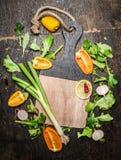 Świezi warzywa i ziele składniki dla smakowitego kucharstwa wokoło pustej tnącej deski na nieociosanym drewnianym tle Fotografia Royalty Free