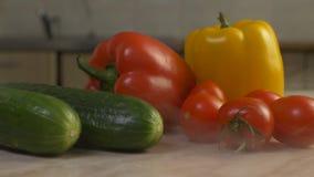 Świezi warzywa, ogórki, pomidory i papryka, kłamają na stole w kuchni zakończenie, od której dmucha chłodno i świeżego zbiory wideo