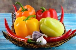 Świezi warzywa, Słodka czerwień, kolor żółty, zieleń, pomarańcze pieprz w koszu na drewnianym tle Czerwonego pieprzu pikantność i Zdjęcia Royalty Free