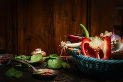 Świezi warzywa w błękitnym koszu, kulinarnej łyżce i składnikach na nieociosanym kuchennym stole nad drewnianym tłem, Fotografia Stock