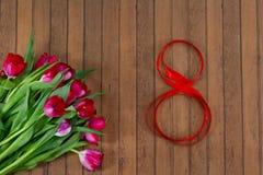 Świezi wiosna tulipany, czerwona taśma na Marzec 8 Obrazy Stock