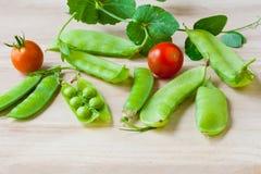 Świezi zieleni grochy i pomidory. obrazy royalty free