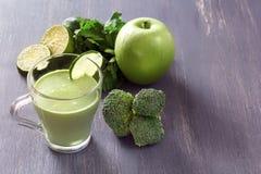 Świezi zieleni smoothies z pietruszką, brokułami, jabłkiem, wapnem i mennicą w szkle na czarnym drewnianym stole z depresja plecy fotografia stock